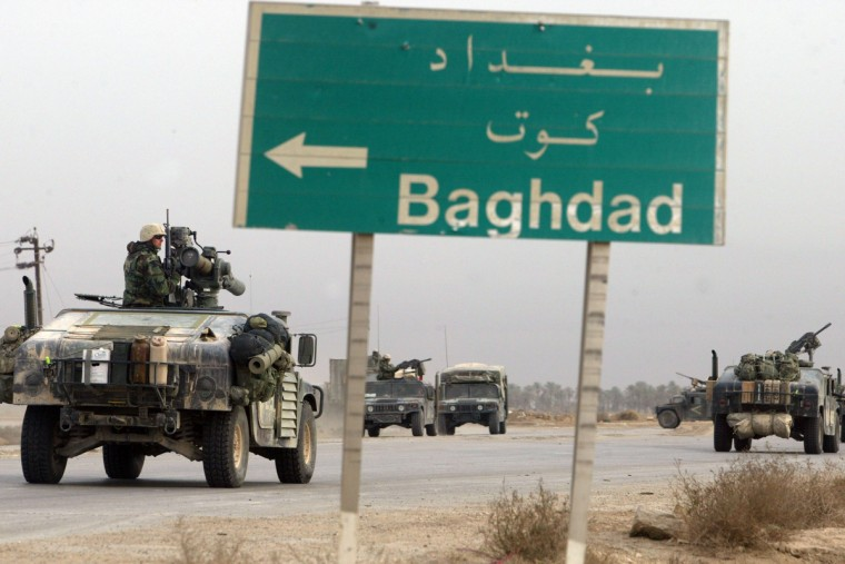 U.S. Marines from the 1st Marine Division pass a sign pointing the way to Baghdad as they continue their march to the capital March 25, 2003 in the southern Iraqi city of Nasiriyah. After two days of running gun battles, the third day seems to be relatively quiet. (Joe Raedle/Getty Images)