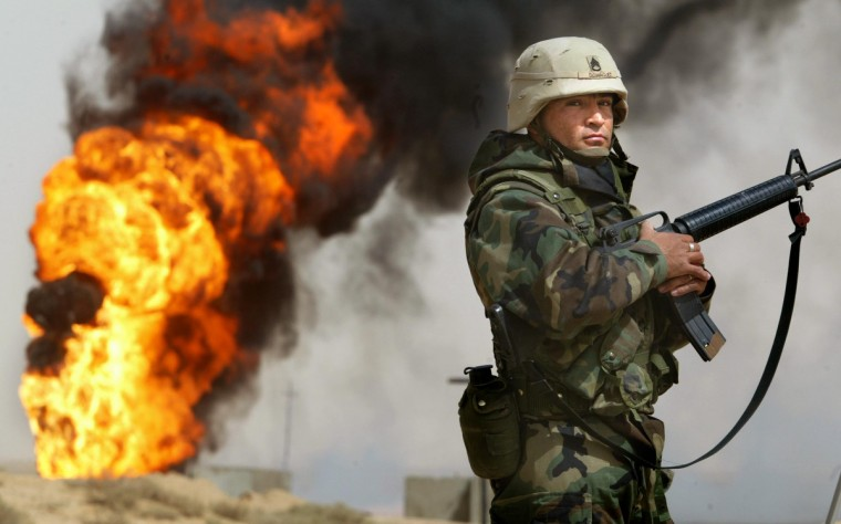 U.S. Army Staff Sergeant Robert Dominguez, of Mathis, Texas, stands guard next to a burning oil well at the Rumayla oil fields March 27, 2003 in Rumayla, Iraq. Several oil wells were set ablaze by retreating Iraqi troops in the Ramayla area, the second largest offshore oilfield in the country, near the Kuwaiti border. (Mario Tama/Getty Images)