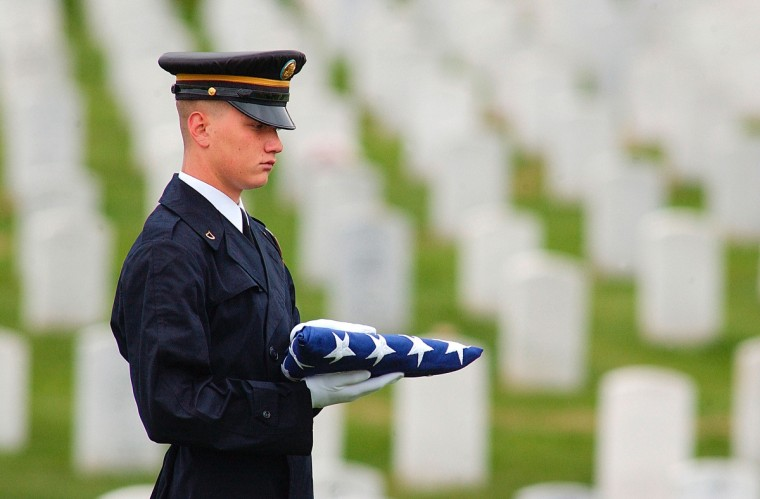 A member of an honor guard holds an American flag as he waits for the funeral of U.S. Army Sergeant First Class Wilbert Davis at Arlington National Cemetery April 18, 2003 in Arlington, Virginia. Davis was killed in a vehicle accident along with journalist Michael Kelly April 3, 2003 in Iraq. (Mike Theiler/Getty Images)