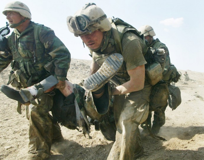 U.S. Marines from Task Force Tarawa carry a wounded Marine during a gun battle March 23, 2003 in the southern Iraqi city of Nasiriyah. The Marines suffered a number of deaths and casualties during gun battles throughout the city. (Joe Raedle/Getty Images)