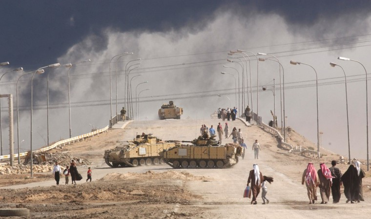 Civilians on foot pass tanks on a bridge near the entrance to the besieged city of Basra March 29, 2003 in Iraq. Baath Party loyalists have taken up positions in Basra, Iraq's second largest city, making it a target of the U.S.-led war on Iraq. (Spencer Platt/Getty Images)