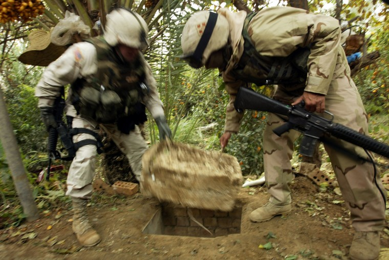 """American soldiers remove a Styrofoam cover that plugged up the """"spider hole"""" where Saddam Hussein hiding when he was captured December 15, 2003 in Ad Dawr, Iraq. Iraq's notorious dictator was captured in a raid at the compound on December 13. (Chris Hondros/Getty Images)"""
