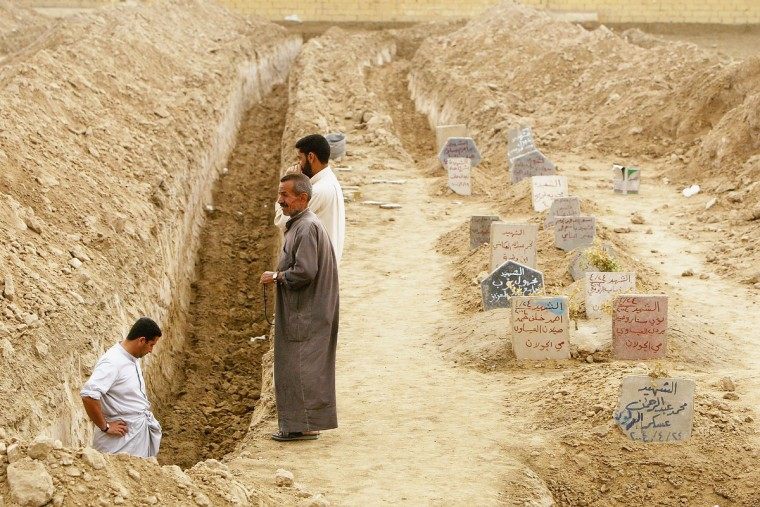 Three men inspect a ditch at an overflowing cemetery built in a soccer arena, on May 3, 2004 in Fallujah, Iraq. An estimated 1,300 Iraqis have been killed during the month-long siege of Fallujah and the death toll continues to rise as residents return home to find more bodies. (Justin Sullivan/Getty Images)