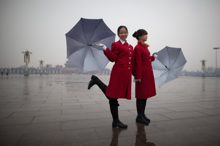 A hostess (L) poses on Tiananmen Square as they wait for delegates to return from the closing session of the Chinese People's Political Consultative Conference (CPPCC) at the Great Hall of the People in Beijing. Thousands of delegates from across China met this week to seal a power transfer to new leaders whose first months running the Communist Party have pumped up expectations with a deluge of propaganda. (Ed Jones/Getty Images)