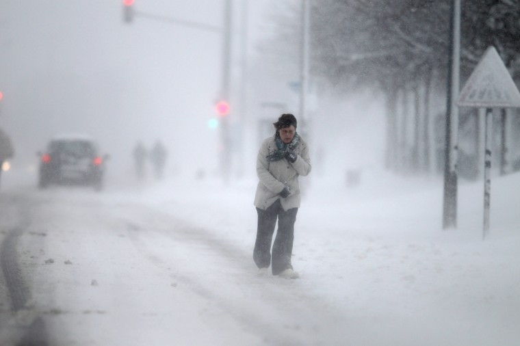"""A woman walks on a snowy road in Caen, northwestern France, during a heavy snow storm on France. Overnight Monday nearly 500 cars were blocked near Cherbourg where snowdrifts piled up 60 centimetres (almost two feet) as winds reached 100 kilometres (more than 60 miles) an hour. Twenty-six regions in northwest and northern France were put on orange alert because of heavy snowfalls, which Meteo France said were """"remarkable for the season because of the expected quantity and length of time"""". (Charly Triballeau/Getty Images)"""