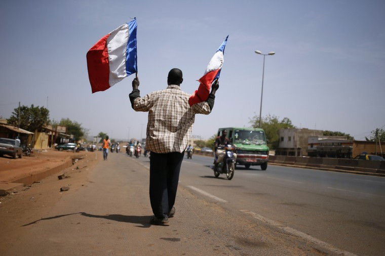 "Traore Madani, 62, walks waving two French flags in the ""Quartier 5"" district of Bamako. Since the start of the French military action in Mali, Traore Madani every day takes to the streets of Bamako to praise on French President Francois Hollande. (Kenzo Tribouillard/Getty Images)"