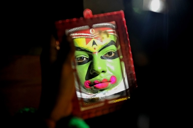A traditional Kathakali performer puts on makeup before an event organized by India's Kerala state Tourism Department in Bangalore. Revenue from tourism brought some 211.25 billion rupees (4 billion USD) to the southern Indian state. (Manjunath Kiran/Getty Images)