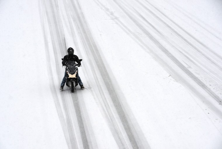 A person rides a scooter on the N118 road around Paris during a heavy snow storm. A heavy late-winter snowstorm hit northwestern Europe on March 12, paralyzing transport, knocking out power to thousands and leaving hundreds stranded in their cars (Franck Fife/Getty Images)