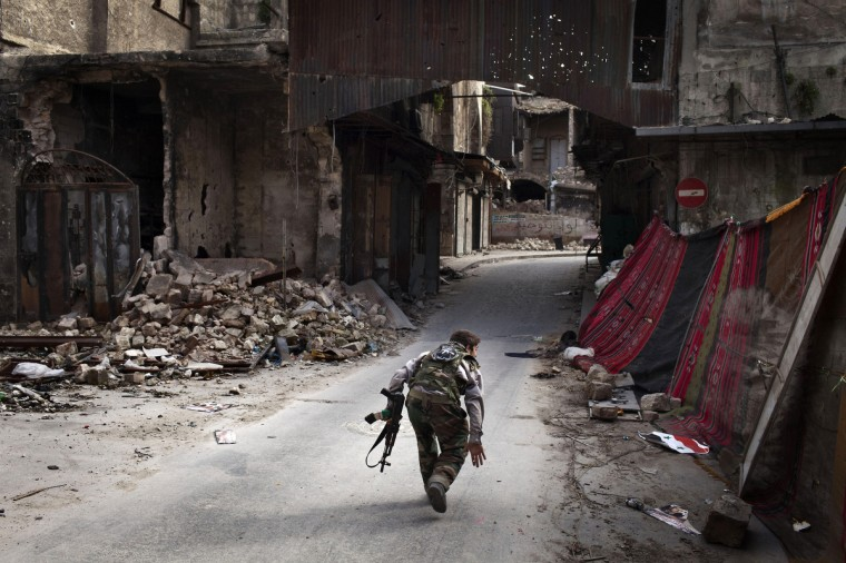 "A Syrian rebel crosses a street while trying to dodge sniper fire in the old city of Aleppo in northern Syria. Syria warned on March 12 it is ready to fight ""for years"" against rebels, as world powers worked on a new initiative to find regime officials suitable for peace talks with the opposition. (JM Lopez/Getty Images)"