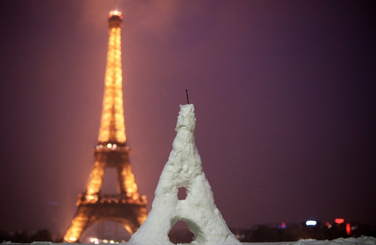 An Eiffel Tower made in snow is seen in front of the Eiffel Tower in Paris. (Franck Fife/Getty Images)