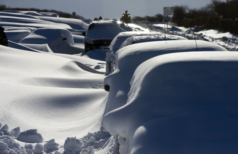 Cars covered in snow are seen on the D901 around Beaumont-Hague, northern France, following a heavy snow storm. Blizzard-like conditions -- coming only eight days before the official start of spring -- knocked out power to thousands of people in France and left motorists stranded in their cars. (Alain Jocard/Getty Images)