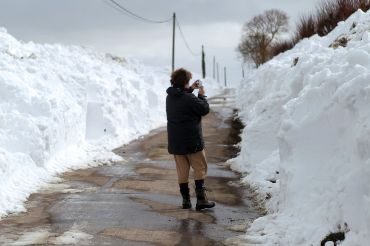 "A woman takes a picture of the snow in Ver-sur-Mer, northern France. More than 68,000 homes were without electricity in France and hundreds of people were trapped in their cars after a winter storm hit with heavy snow, officials and weather services said on March 12. Twenty-six regions in northwest and northern France were put on orange alert because of heavy snowfalls, which Meteo France said were ""remarkable for the season because of the expected quantity and length of time"". (Charly Triballeau/Getty Images)"