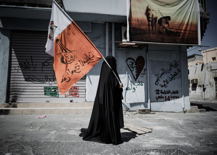 A Bahraini woman holds up her national flag decorated with anti-government slogans in the village of Jidhafs, west of Manama, on March 14, 2013. Bahraini police clashed with youths protesting against the deployment into a third year of a Gulf military force that backed Manama's bid to crush a Shiite-led uprising, witnesses said. (Mohammed Al-Shaikh/Getty Images)
