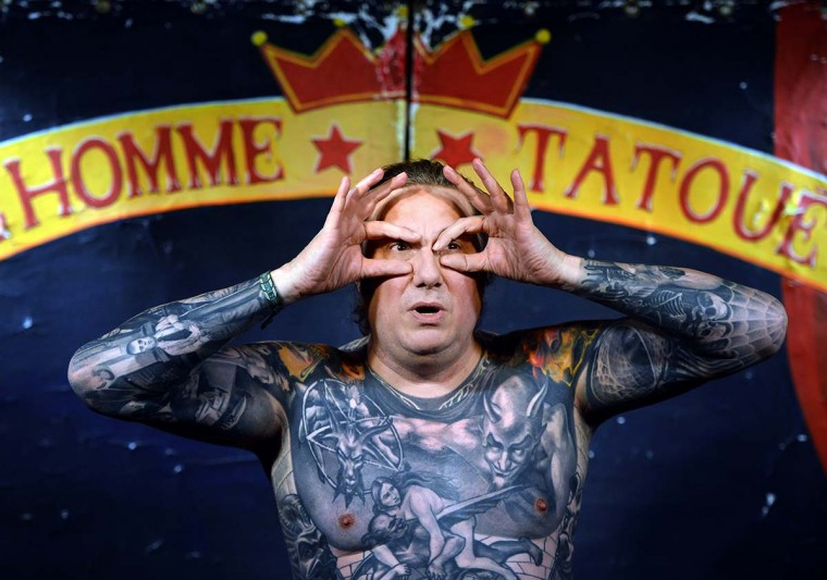 "French artist with a completely tattooed body, Pascal Tourain, aka Bulldozer, performs on March 13, 2013 during his show ""L'Homme Tatoue"" (Tattooed Man) in Paris. The World tattoo 2013 will take place in Paris from March 22 to 24, 2013. Some 10.000 people are expected to attend the event. (Miguel Medina/AFP/Getty Images)"