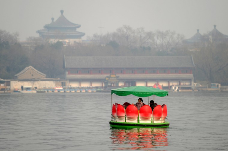 """A family cruse at a park in Beijing. A Chinese city is searching for a foreign traveller to become a """"modern Marco Polo"""", with a 40,000 euro ($52,000) salary on offer to the winner, a tourism official said on March 13. (Wang Zhao/Getty Images)"""