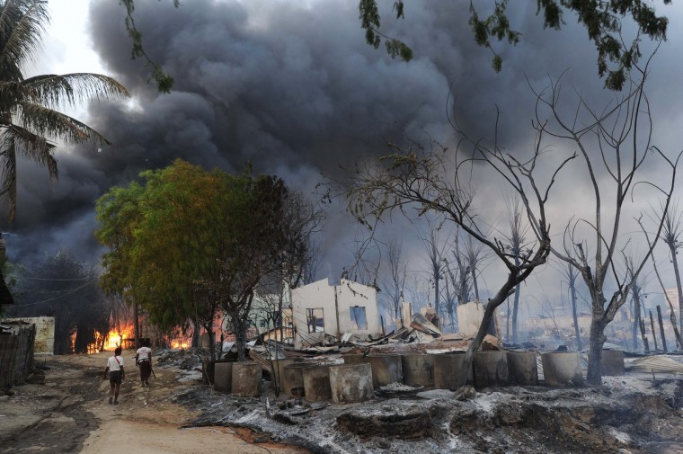 Myanmar residents walk past destroyed houses as black smoke rises from burning buildings in riot-hit Meiktila, central Myanmar. At least 10 people have been killed in riots in central Myanmar, an MP said, prompting international concern at the country's worst communal unrest since a wave of Buddhist-Muslim clashes last year. (Soe Than Win/Getty Images)