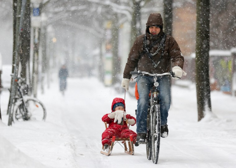 A man on a bike pulls a child on a sledge through the snow in Berlin. Temperatures in the German capital were around the freezing point. (Kay Nietfeld/Getty Images)