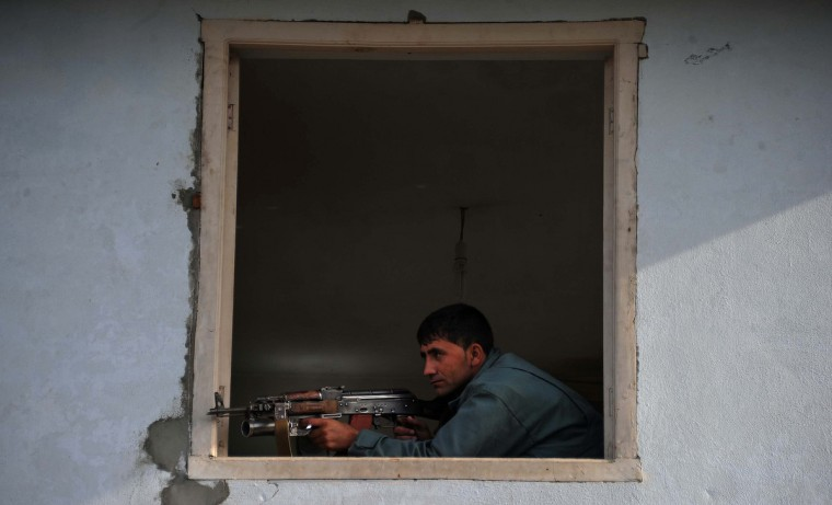 An Afghan policeman takes position at the site of a suicide attack in Jalalabad. A group of seven suicide bombers attacked a police base in the eastern Afghan city of Jalalabad, killing five officers, police said. One bomber set off a large explosion at the entrance of the quick reaction police headquarters before two bombers blew themselves up inside the facility and four others died in a gun fight with police. (Noorullah Shirzada/Getty Images)