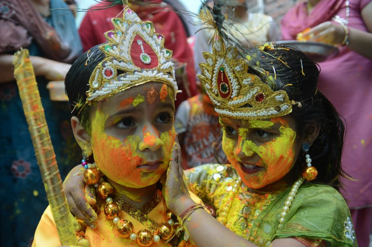 Indian children dressed as Lord Krishna (L) and Radha play with colored powder during a Holi celebration at a temple in Amritsar. Holi, also called the Festival of Colors, is a popular Hindu spring festival observed in India at the end of the winter season on the last full moon day of the lunar month and falls on March 27 this year. (Narinder Nanu/Getty Images)