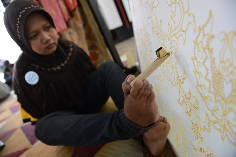 Ayu, a 22 year old handicapped Indonesian applies wax with her foot to create a batik design with a canting or wax pen on a cotton fabric during a demonstration in Jakarta. Ayu born with a congenital handicap overcame her disability when she studied in regular public school and at the age of 17 learnt the art of batik making. Ayu finishes wax patterns on a cloth in about one week. Ayu and her family lives in Solo city, a key batik fabric producing area in central Java island. (Romeo Gacad/Getty Images)