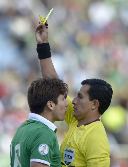 Chile's referee Enrique Osses shows the yellow card to Bolivia's Ronald Raldes during the Brazil 2014 FIFA World Cup South American qualifier football match against Argentina, at the Hernando Siles stadium in La Paz. (Juan Mabromata/Getty Images)
