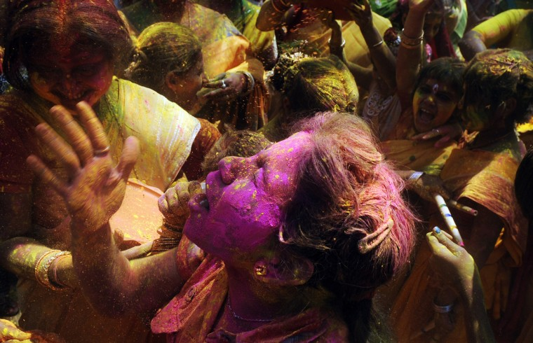 Indian Hindu devotees dance and play with colored powder on the side of a road during Holi celebrations in Kolkata. Holi, also called the Festival of Colours, is a popular Hindu spring festival observed in India at the end of the winter season on the last full moon day of the lunar month. (Dibyangshu Sarkar/Getty Images)