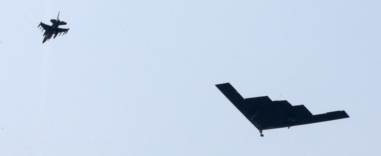 "A US B-2 stealth bomber (R) flies over a US air base in Pyeongtaek, south of Seoul as part of South Korea-US joint military exercise. Two nuclear-capable US B-2 stealth bombers flew what the US military described as ""deterrence"" missions over South Korea on March 28, in a move sure to further inflame tensions with North Korea. (Yonhap/Getty Images)"