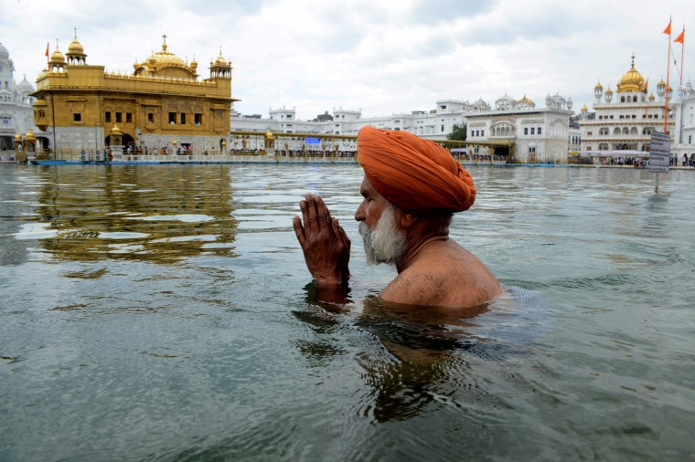 An Indian Sikh devotee bathes in the holy sarover (water tank) on the occasion of 'Hola Mohalla' at The Golden Temple in Amritsar. Hola Mohalla is a three day Sikh festival, in which Nihang Sikh 'warriors' perform Gatka (mock encounters with real weapons), tent pegging and bareback horse-riding, which usually falls in March following the Hindu festival of Holi. (Narinder Nanu/Getty Images)