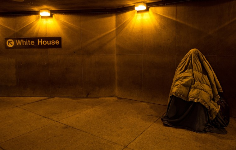 A homeless person covered in blankets for warmth, sleeps at the entrance of a Metro station near the White House in Washington, DC. (Karen Bleir/Getty images)