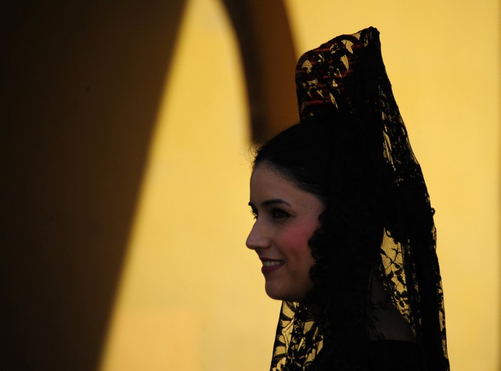 A woman wearing the traditional Mantilla walks under the Macarena arch during the Holy Week in Sevilla. Christian believers around the world mark the Holy Week of Easter in celebration of the crucifixion and resurrection of Jesus Christ. (Cristina Quicler/Getty Images)