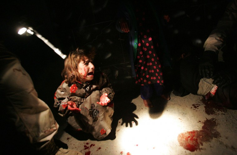 Samar Hassan screams after her parents were killed by U.S. Soldiers with the 25th Infantry Division in a shooting January 18, 2005 in Tal Afar, Iraq. The troops fired on the Hassan family car when it unwittingly approached them during a dusk patrol in the tense northern Iraqi town. Parents Hussein and Camila Hassan were killed instantly, and a son Racan, 11, was seriously wounded in the abdomen. Racan, who lost the use of his legs, was treated later in the U.S. (Chris Hondros/Getty Images)