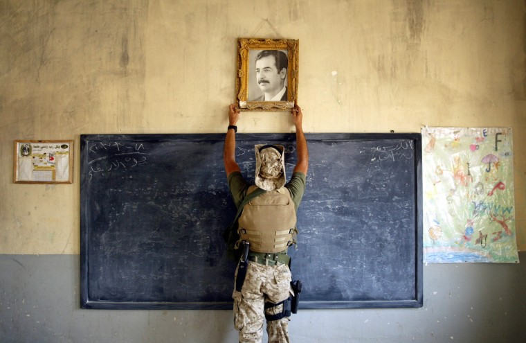 A U.S. Marine pulls down a picture of Saddam Hussein at a school April 16, 2003 in Al-Kut, Iraq. A combination team of Marines, Army and Special Forces went to schools and other facilities in Al-Kut looking for weapons caches and unexploded bombs in preparation for removing and neutralizing them. (Chris Hondros/Getty Images)
