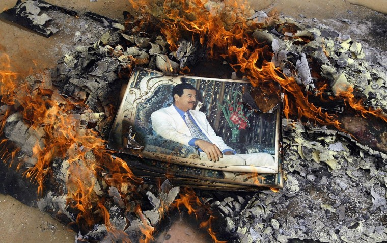 A picture of Saddam Hussein is burned by U.S. Marines April 7, 2003 in Qal'at Sukkar, Iraq. The 24th Marine Expeditionary Unit entered the town looking for weapons and destroying pictures of Saddam Hussein. (Chris Hondros/Getty Images)