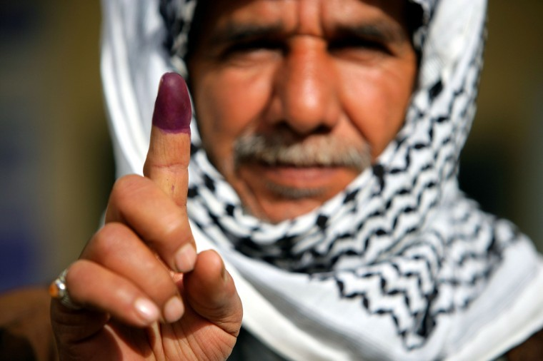 Iraqi man in Najaf displays his finger to the camera on January 30, 2005 in Najaf, Iraq. The purple dye indicates that he has just voted in Iraq's first elections. The Shiite holy city of Najaf enjoyed a calm election day with no violence and a good voter turnout reported at many voting stations. Najaf is an important holy city in the Shiite religion and the city has been secured against election violence. (Brent Stirton/Getty Images)