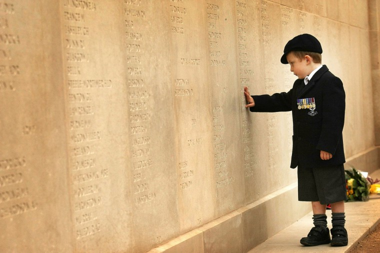 Five-year-old Alex Ward, of Norfolk, Britain, proudly wears his fathers medals as he searches for his father's name on the wall of the Armed Forces Memorial on 12 October, 2007, Lichfield, England. Warrant Officer Colin Ward of the Royal Military Police was killed in Iraq in 2003. (Christopher Furlong/Getty Images)