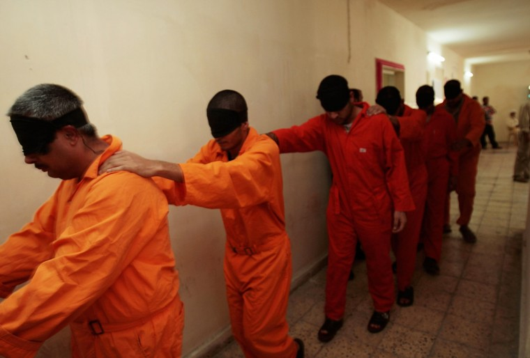 Arrested Iraqi men who've been chosen to appear before an Iraqi judge to be arraigned are led in blindfolded to the court building November 6, 2007 in Baghdad, Iraq. Around 300 Iraqi men who have been swept up in raids by Iraqi and US forces--often on charges of insurgent activity or organized crime such as kidnapping rings--are detained at a sparse rudimentary jail on a combined US-Iraqi military base, and about five to ten a day are outfitted in orange jumpsuits and brought before a panel of judges at a nearby makeshift courtroom. Judges look over each men's file of evidence, hear the accused's statement, and route the case accordingly. Defendants are represented by an Iraqi woman lawyer, the Iraqi equivalent of a public defender. (Chris Hondros/Getty Images)