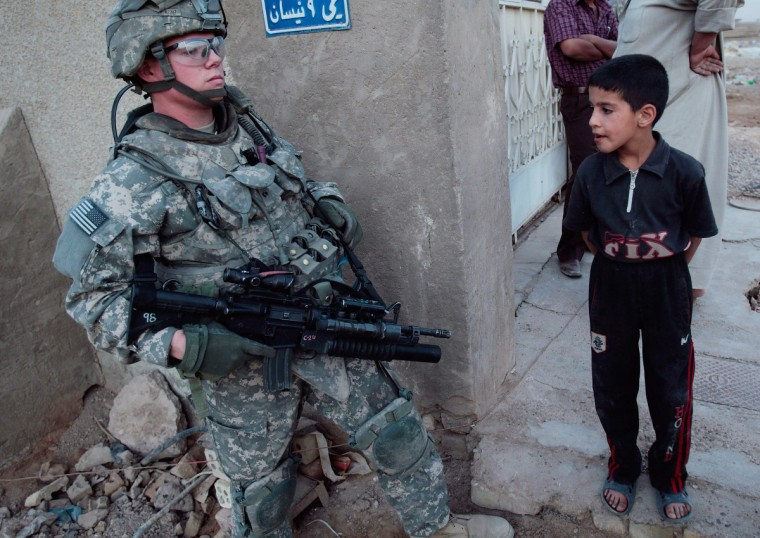 An Iraqi boy (R) looks over a U.S. soldier during a pause in a foot patrol in the Baladiyat neighborhood May 15, 2008 in Baghdad, Iraq. Tenth Mountain Division soldiers in the area take daily joint patrols with the Iraqi National Police, in the ongoing effort to build up stable national Iraqi security institutions aligned with the national government. (Chris Hondros/Getty Images)
