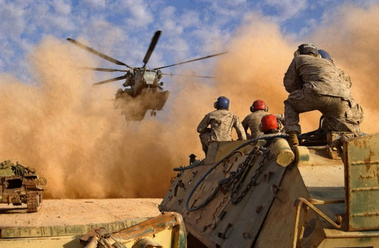 Support Team Marines watch for the approach of a CH-53E Super Stallion from Marine Medium Helicopter Squadron 166 (reinforced), Marine Aircraft Group 16, while sitting on an old Iraqi armored personnel carrier. (Getty Images)