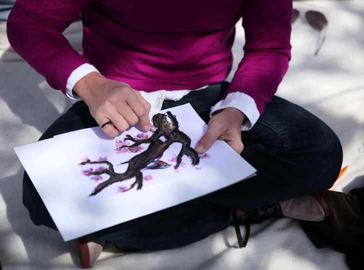 March 25, 2011: A man draws as cherry trees start to bloom by Tidal Basin in Washington, DC. (Alex Wong/Getty Images)