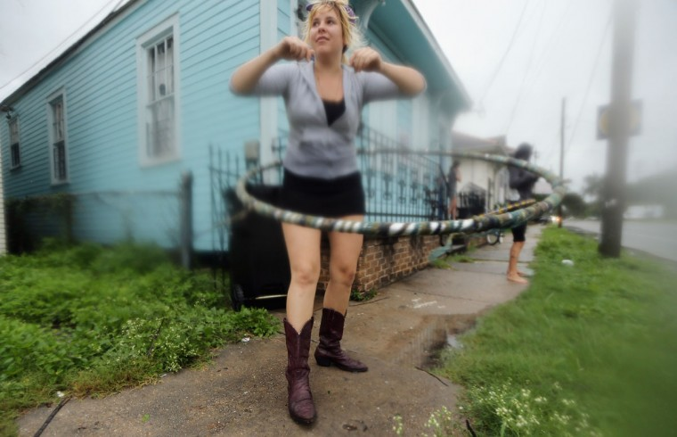 August 28, 2012: Kat Soulagnet hula hoops at a 'Hurricane Party' in the Upper Ninth Ward in New Orleans, Louisiana. (Mario Tama/Getty Images)