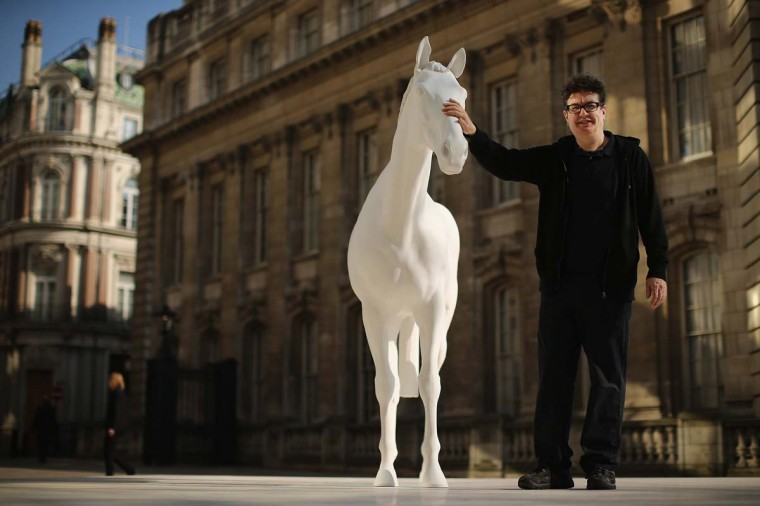 Artist Mark Wallinger poses beside his new sculpture 'The White Horse' outside the headquarters of The British Council on the Mall on March 5, 2013 in London, England. The British Council unveiled the marble and resin, life-size sculpture representing a thoroughbred racehorse, as it announced a GBP 7 million investment in work connecting UK-based creative talent overseas. (Dan Kitwood/Getty Images)