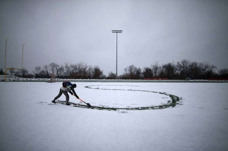 Student Hunter Gallagher uses a shovel to write a letter from his girlfriends name in the snow on the football field at Catholic University on March 6, 2013 in Washington, DC. A late-season winter snowstorm is forecasted to hit the Washington area and is expected to dump 5 to 10 inches of snow. (Mark Wilson/Getty Images)