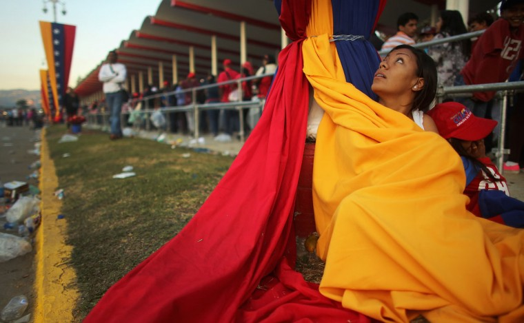 A woman keeps warm wrapped in the national flag as people wait in line before the start of the funeral for Venezuelan President Hugo Chavez outside the Military Academy on March 8, 2013 in Caracas, Venezuela. Countless Venezuelans have paid their last respects to Chavez and more than 30 heads of state are expected to attend the funeral today. (Mario Tama/Getty Images)