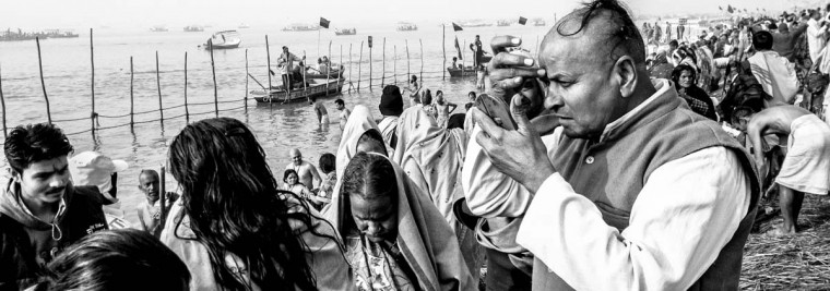 Hindu devotees dress themselves after having bathed on the banks of Sangam on January 13, 2013 in Allahabad, India. (Daniel Berehulak/Getty Images)