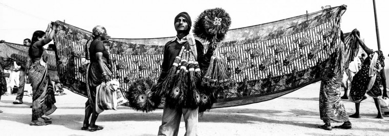 A man sells peacock feathers as Hindu devotee hold out sarees to dry after having bathed on the banks of Sangam on January 13, 2013 in Allahabad, India. (Daniel Berehulak/Getty Images)