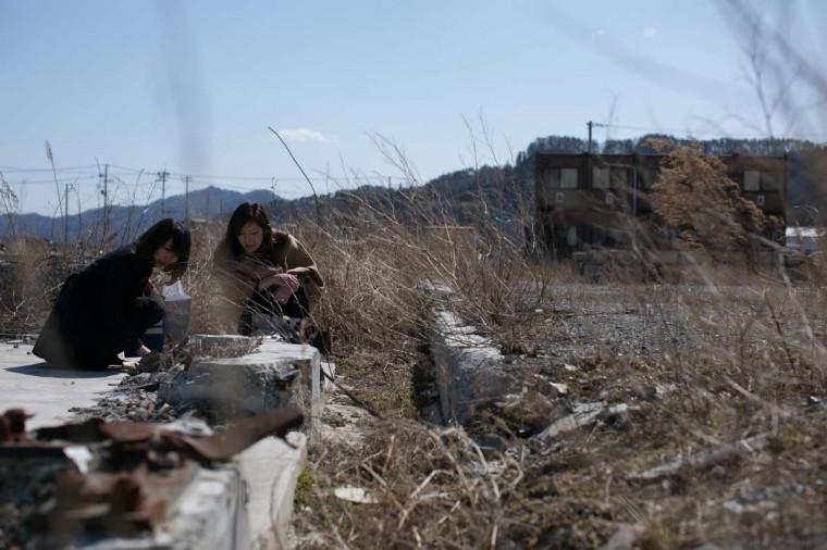 Eri Hashimoto (L) and Shizue Hashimoto pray for their father, who is still missing, where their house used to stand on March 11, 2013 in Ootsuti, Iwate prefecture, Japan. On March 11 Japan commemorates the second anniversary of the magnitude 9.0 earthquake and tsunami that claimed more than 18,000 lives. (Ken Ishii/Getty Images)