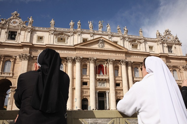 Nuns stand in front of St Peter's Basilica in St Peter's Square on March 12, 2013 in Vatican City, Vatican. Pope Benedict XVI's successor is being chosen by the College of Cardinals in Conclave in the Sistine Chapel. The 115 cardinal-electors, meeting in strict secrecy, will need to reach a two-thirds-plus-one vote majority to elect the 266th Pontiff. (Dan Kitwood/Getty Images)