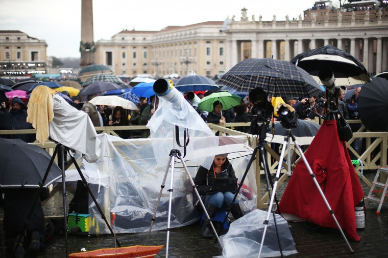 Photographers' cameras are protected with waterproof material and umbrellas as the media awaits news from the papal conclave in St Peter's Square on March 13, 2013 in Vatican City, Vatican. (Peter Macdiarmid/Getty Images)