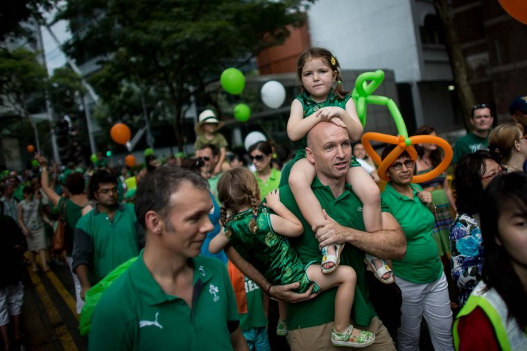 A man carries children down the street during the St Patricks Day Parade at Boat Quay on March 17, 2013 in Singapore. Singapore's Irish community gathered at Boat Quay for a three-day-long St Patrick's Day Street Festival which featured street performances, buskers, and Irish food and drink. (Chris McGrath/Getty Images)