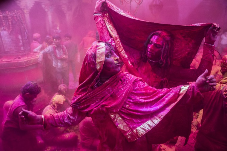 Transgender Hindu devotees dance as others play with color during Lathmar Holi celebrations on March 21, 2013 in the village of Barsana, near Mathura, India. (Daniel Berehulak/Getty Images)